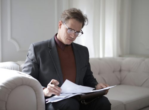 classy-executive-male-reading-papers-on-couch-3760514.jpg